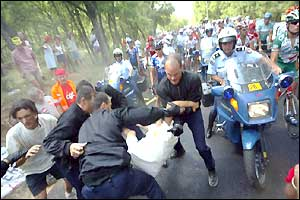 Security officers try to remove protesters from the road as they block the peloton