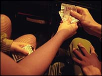 A client hands cash to a prostitute