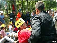 Police drag away protesters demonstrating against Jose Bove's sentence at Tour de France