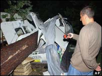 A man looks at a trailer destroyed by a fallen tree at the La Rive campsite near Biscarosse, south-western France