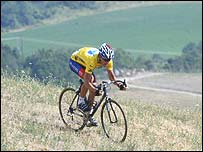 Lance Armstrong was forced to cycle through a field on Monday after narrowly missing a crash involving one of his closest rivals