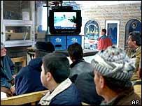Iraqi Kurds watch an Arabic satellite TV station during the war