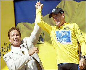 Arnold Schwarzenegger  raises Lance Armstrong's hand on the podium after the American retained the yellow jersey