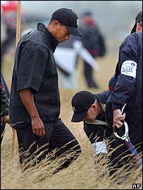 Course officials help Tiger Woods search for his ball at the 1st hole