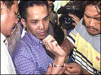 Police struggle to remove handcuffs from Ali Imron