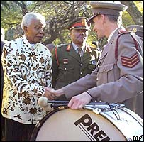 Nelson Mandela shakes hand with a member of a military band