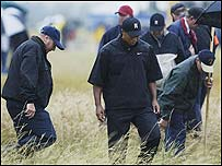 Tiger Woods searches for his ball on the first hole