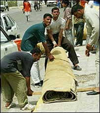 Looters try to carry off a hotel carpet in Basra