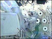 Yuri Malenchenko connects electrical and communication cables between the Zarya and Zvezda modules of the International Space Station during a televised spacewalk