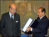 Italian PM and current EU President Silvio Berlusconi (right) receives the draft EU constitution from Valery Giscard d'Estaing