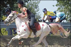 A spectator on a white horse painted with red polka dots rides alongside Lance Armstrong