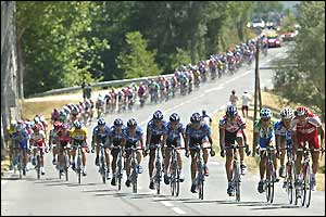 The peloton are stretched out into the distance along the road