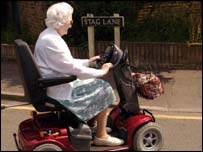An elderly woman on a motorised scooter