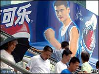 Shanghai residents walks before a billboard of American giant beverage company Pepsi