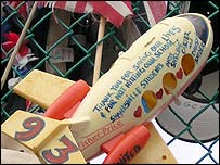 Toy plane attached to makeshift memorial. Writing on plane says: 'Thank you for saving our lives & for not hitting our school.'