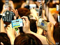 Japanese holding up cameras and mobiles