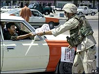 A US soldier hands a leaflet to Iraqis in a car