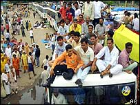 Pilgrims crowd on top of a bus as they wait to make their pilgrimage to Amarnath