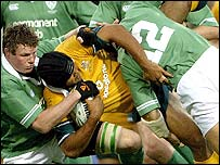Toutai Kefu of Australia is brought crashing down by the Irish defenders