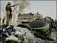 A U. soldier directs cleaning up operations of the wreckage of US army Humvees in Baghdad, Iraq, 21 July 2003