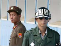A North Korean soldier (left) looks at a South Korea soldier standing guard at the Panmunjom truce village