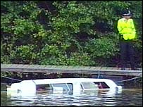 A police officer standing by the boat that capsized in the River Severn in Worcestershire