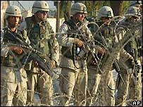 US soldiers on patrol behind wire fence in Iraq