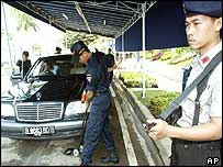 security guards search a car for bombs before it enters JW Marriott Hotel