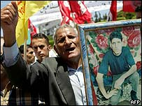 Palestinian man shouts slogans while holding a portrait of his imprisoned son during a demonstration in support of the Palestinian prisoners in Israeli jails, 21 July 2003 in Gaza City