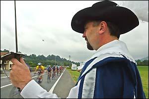A spectator dressed as a musketeer watches the peloton pass by
