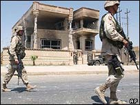 Soldiers outside the villa where Saddam Hussein's sons were killed