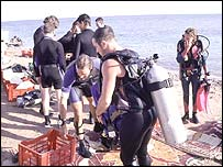 Scuba divers prepare for a dive