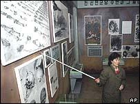A North Korean attendant pointing to photographs from the Korean War
