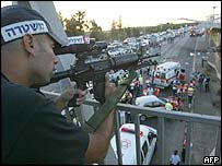 A police marksman overlooks the scene of the blast