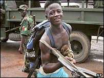 A young Liberian rebel carries a puppy in Kakata
