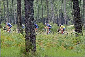 The US Postal team ride through a forest on their way to Bordeaux
