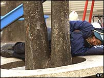 A homeless man sleeps at a park in Tokyo's Asakusa shopping district