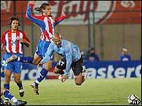 Carlos Paredes de Paraguay lucha por la pelota con Rubén Olivera de Uruguay.