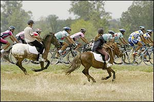 Two people on horseback ride alongside the peloton
