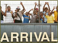 Solomon Islands locals wave from the observation deck while watching Australian troops disembark