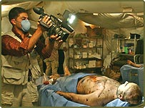 A cameraman films a corpse said to be of former dictator Saddam Hussein's son, Uday