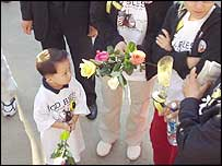 Boy holds flowers at the ceremony in New York