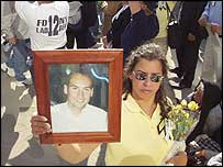 Woman hold a framed picture of one of the victims of the attacks