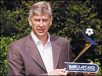 Arsene Wenger poses with the manager of the month award for May