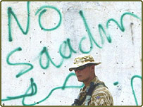 British Royal Air Force Regiment patrol pass graffiti reading 'No Saddam' in the southern Iraqi town of Safwan