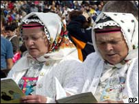 Women in traditional costumes sing prior to a mass celebrated by the pope in Roznava, Slovakia