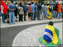 An MST activist sits swathed in the Brazilian flag by a food queue near Sao Paulo