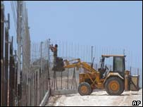 Israelis work on building a fence to separate Israel and the Palestinian territories near the city of Qalqilya