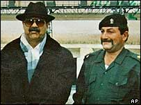 Bodyguard Adnan Abdullah Abid al-Musslit, right, standing next to Saddam Hussein