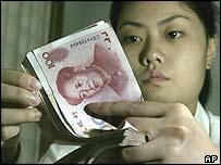 A bank worker counts Chinese yuan